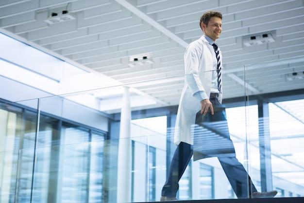 Médecin de sexe masculin marchant avec rapport de radiographie dans le couloir