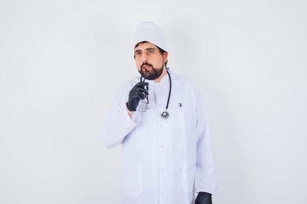 Médecin de sexe masculin mordant des lunettes en uniforme blanc et regardant concentré. vue de face.