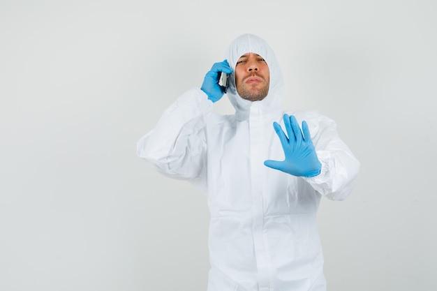 Médecin de sexe masculin parlant au téléphone mobile avec geste d'arrêt en combinaison de protection