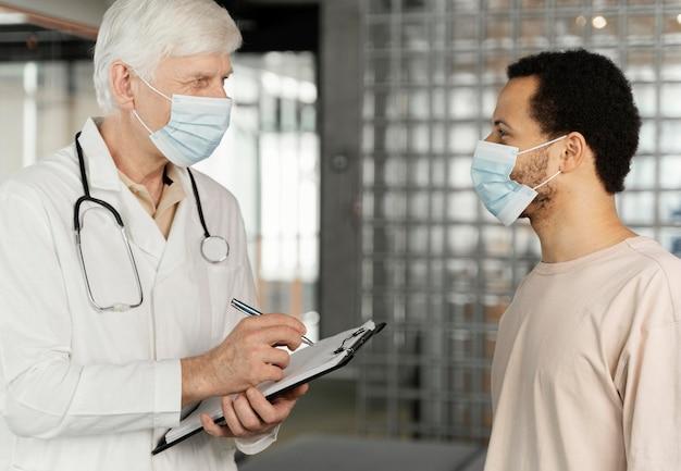 Médecin de sexe masculin, parler avec le patient