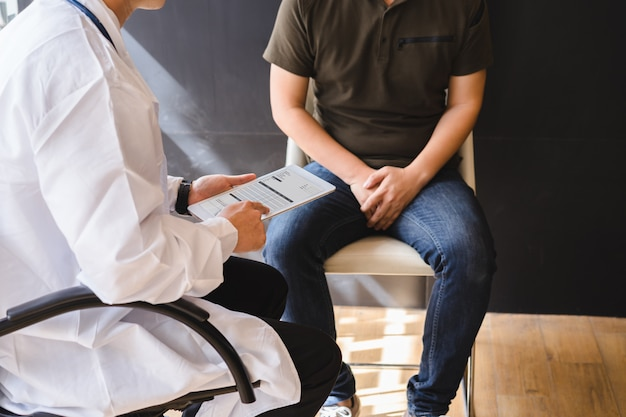Un médecin de sexe masculin et un patient atteint d'un cancer des testicules discutent d'un rapport de test de cancer du testicule. cancer du testicule et cancer de la prostate.