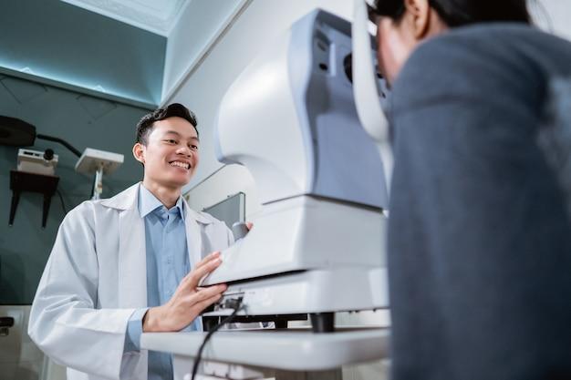 Un médecin de sexe masculin et une patiente faisant un examen de la vue à l'aide d'un appareil dans une clinique ophtalmologique