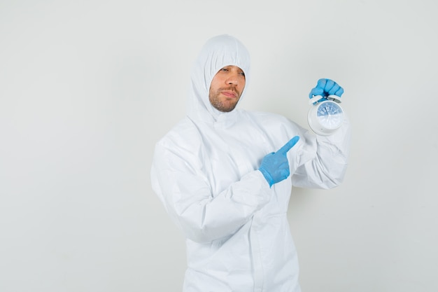 Médecin de sexe masculin pointant sur réveil en tenue de protection
