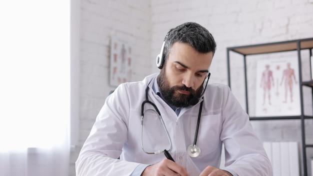 Médecin de sexe masculin portant une blouse blanche consultant le patient à distance en ligne à l'aide d'un casque. vue webcam.