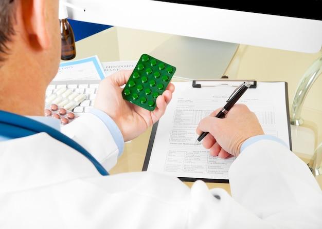 Médecin de sexe masculin prend des pilules et écrit la mise au point sélective sur ordonnance