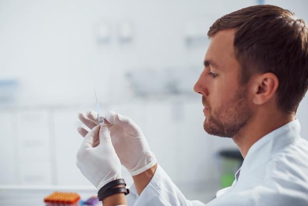Un médecin de sexe masculin avec une seringue se prépare pour le prélèvement sanguin dans la salle de la clinique.