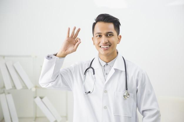 Médecin de sexe masculin souriant gesticulant bien