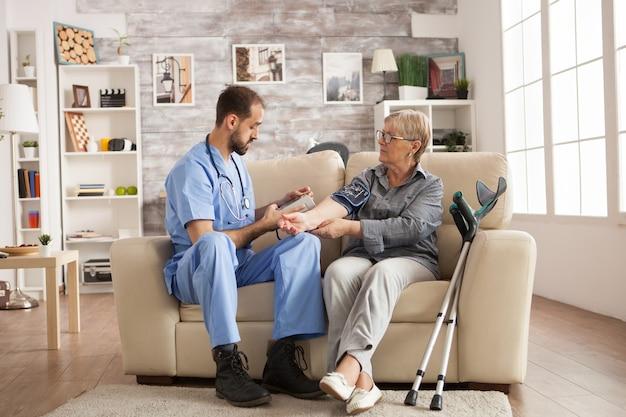 Médecin de sexe masculin avec stéthoscope autour du cou prenant la pression artérielle d'une femme âgée en maison de retraite.