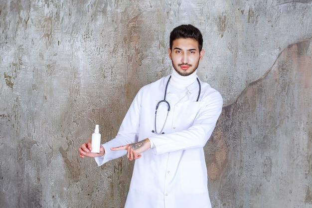 Médecin de sexe masculin avec stéthoscope tenant une bouteille de désinfectant pour les mains blanc.