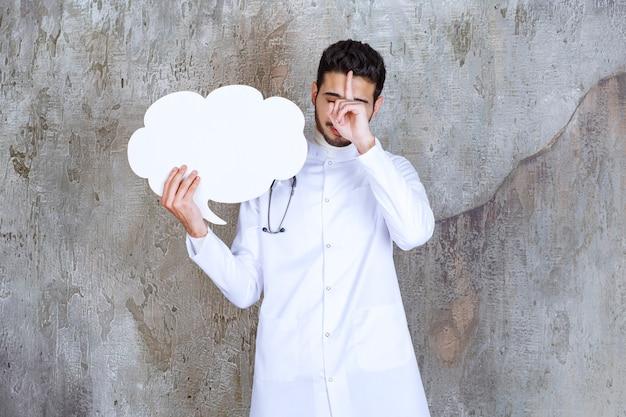 Médecin de sexe masculin avec stéthoscope tenant un panneau d'information en forme de nuage vierge et a l'air réfléchi.