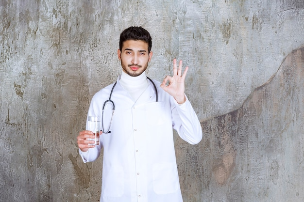 Médecin de sexe masculin avec stéthoscope tenant un verre d'eau pure et montrant un signe positif de la main