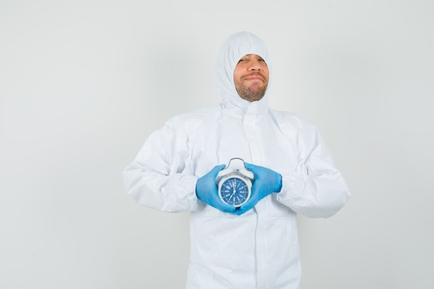 Médecin de sexe masculin tenant un réveil en tenue de protection