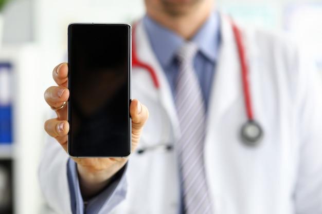 Médecin de sexe masculin tenant un téléphone portable et le montrant au bureau. technologie moderne de matériel médical et concept de communication. thérapeute utilisant des informations de recherche de smartphone