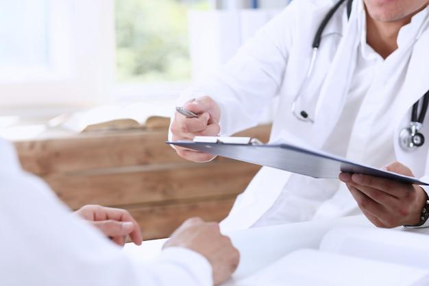 Médecin de sexe masculin tenir un stylo argenté et un bloc d'affichage.