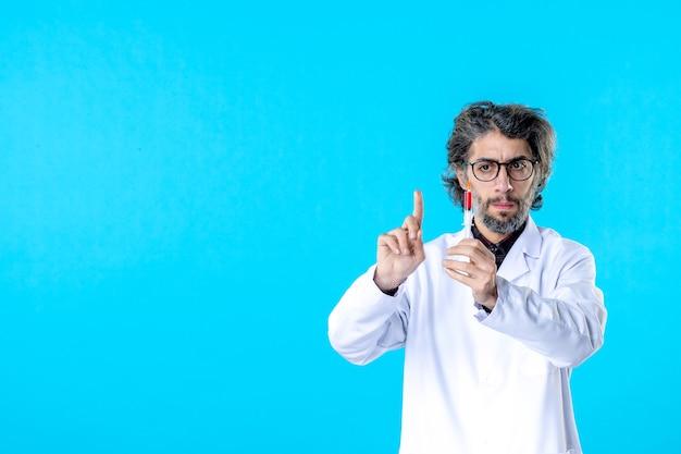 Médecin de sexe masculin vue de face préparant l'injection sur bleu
