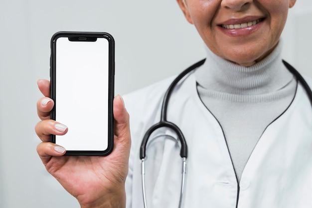 Médecin smiley tenant un téléphone vide