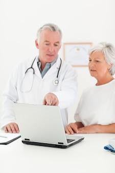 Médecin et son patient en regardant l'ordinateur portable