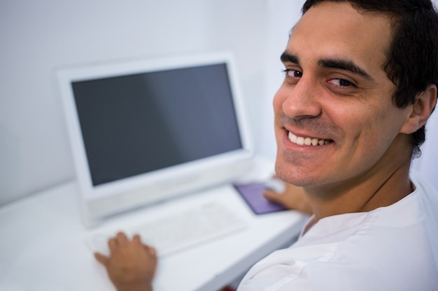 Médecin souriant à l'aide d'un ordinateur de bureau à la clinique