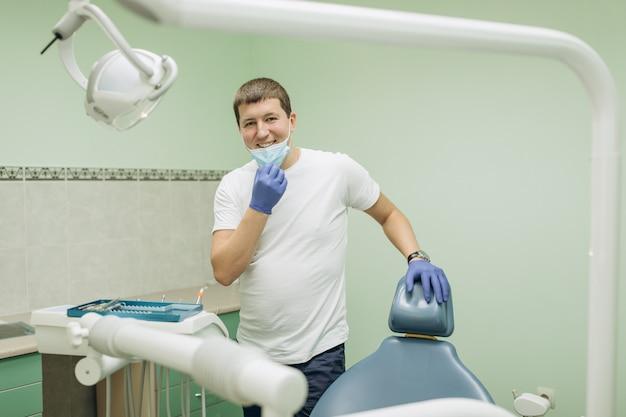 Médecin souriant dans des gants médicaux en clinique dentaire