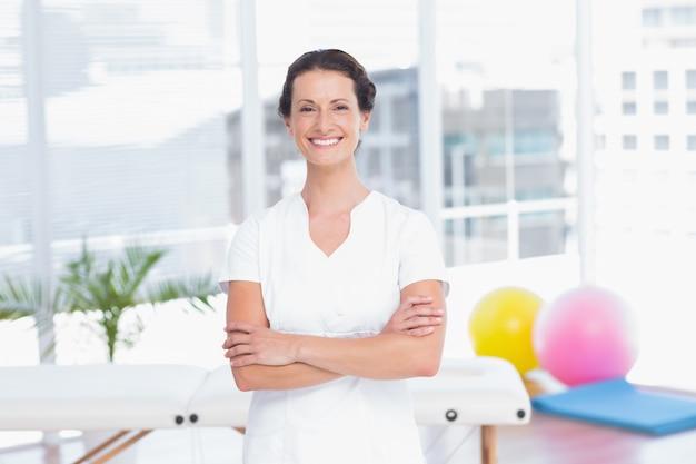 Médecin souriant, debout, bras croisés et regardant le cabinet médical de la caméra