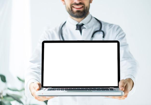 Médecin souriant démontrant un ordinateur portable