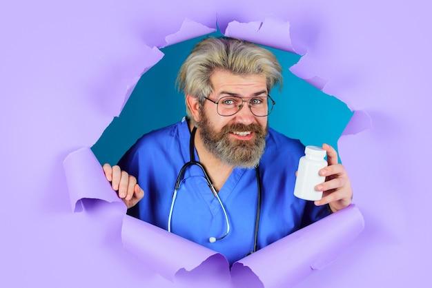 Médecin souriant perçant le fond violet tenant une bouteille de pilules