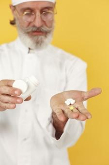 Médecin souriant avec des pilules. isolé.