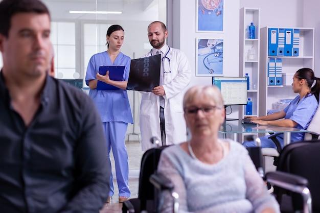 Médecin spécialiste communiquant un examen radiographique à une infirmière lors de l'écriture d'un traitement sur un presse-papiers contre la maladie pour une femme âgée en fauteuil roulant