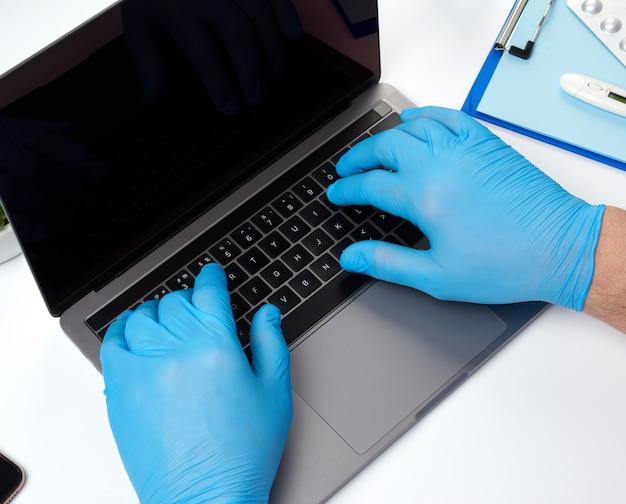 Médecin spécialiste des gants médicaux en latex bleu travaillant sur un ordinateur portable, concept de maintenance à distance