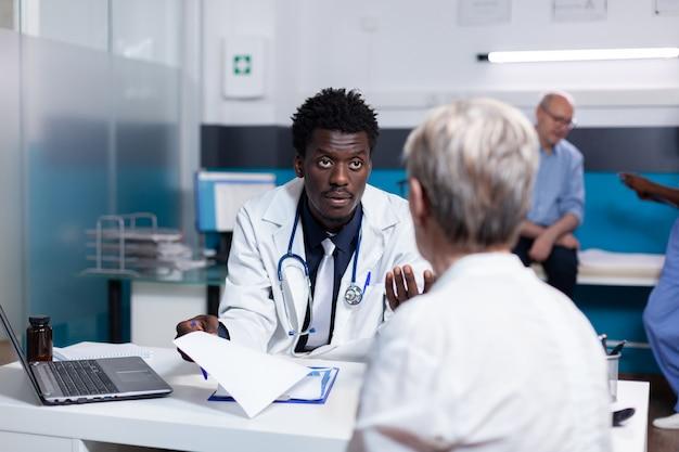 Médecin spécialiste noir consultant un patient âgé au bureau