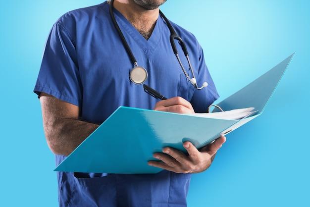 Médecin avec stéthoscope écrit sur le dossier médical sur bleu