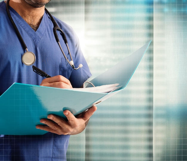 Médecin avec stéthoscope écrit sur le dossier médical