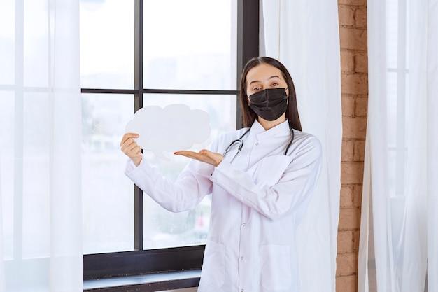 Médecin avec stéthoscope et masque noir tenant un tableau de réflexion en forme de nuage blanc.