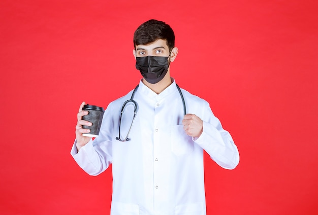 Médecin avec stéthoscope en masque noir tenant une tasse de café à emporter noire et montrant son poing.