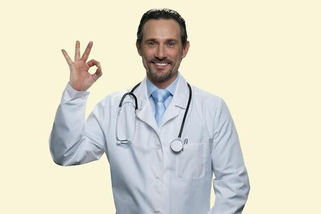 Médecin avec stéthoscope montre un geste correct. isolé sur fond jaune.