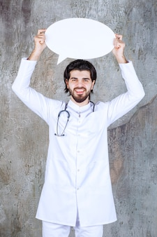 Médecin avec un stéthoscope tenant un tableau d'information vierge ovale.