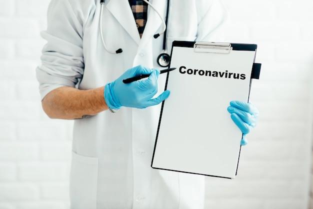 Un médecin avec une tablette sur fond blanc montre le nom de la maladie avec un stylo coronavirus