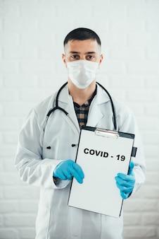 Un médecin avec une tablette sur fond blanc montre le nom de la maladie avec un stylo covid-19