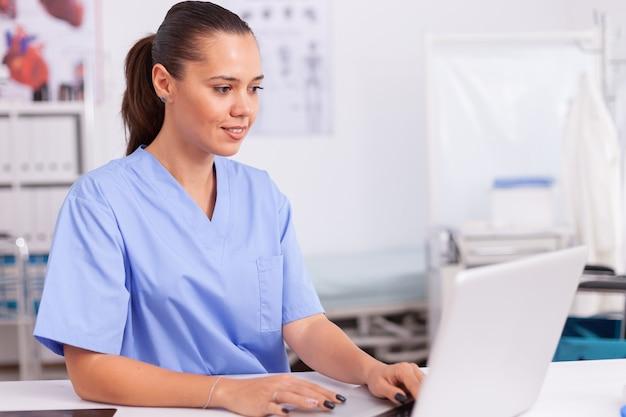 Médecin tapant sur un ordinateur portable assis au bureau en uniforme bleu. médecin de santé utilisant l'ordinateur dans une clinique moderne regardant le moniteur, la médecine, la profession, les gommages.