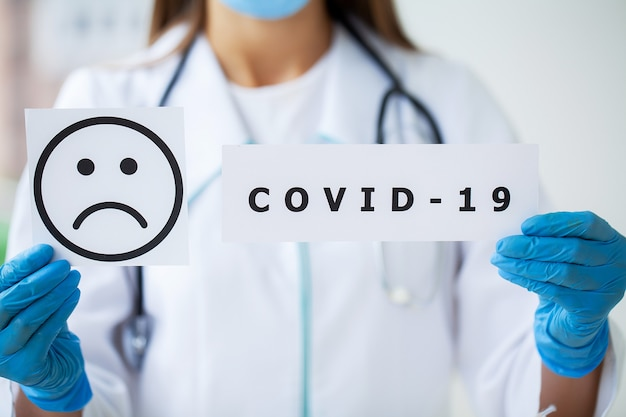 Médecin tenant une carte papier avec texte covid-19