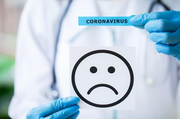 Médecin tenant une carte papier avec texte covid-19.