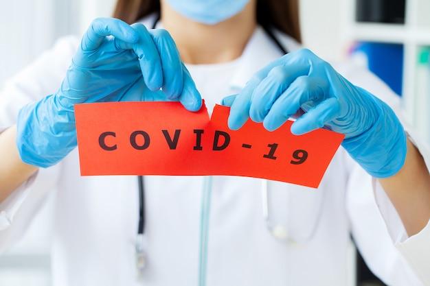 Médecin Tenant Une Carte Papier Avec Texte Covid-19. Photo Premium