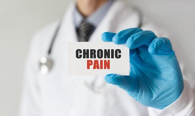 Médecin tenant une carte avec texte douleur chronique