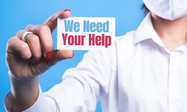 Médecin tenant une carte avec texte nous avons besoin de votre aide