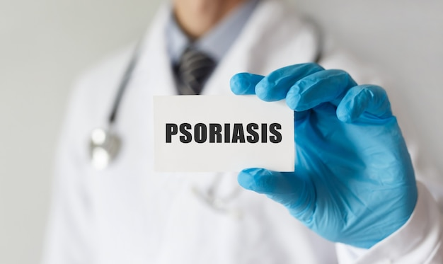 Médecin tenant une carte avec texte psoriasis, concept médical