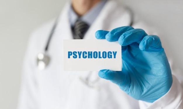 Médecin tenant une carte avec texte psychologie, concept médical