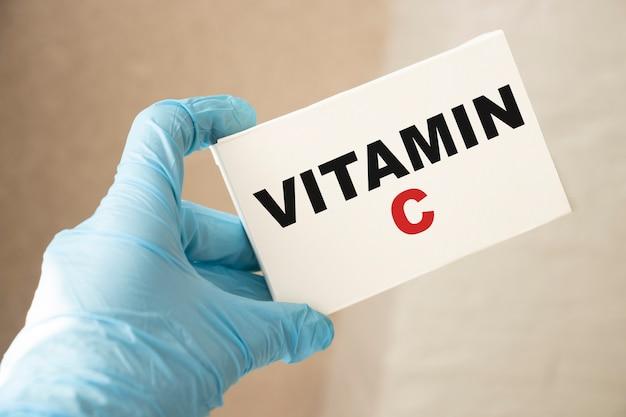 Médecin tenant une carte avec de la vitamine c, concept médical