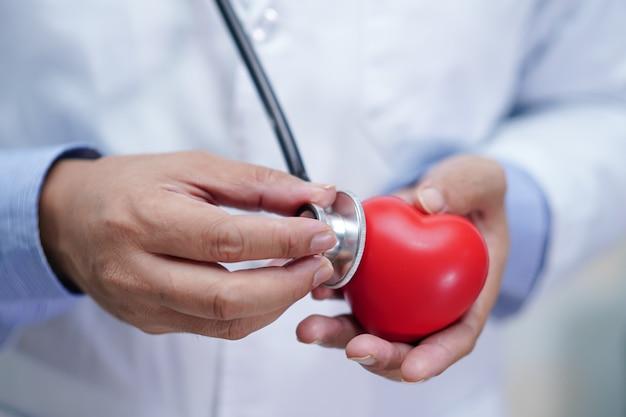 Médecin tenant un coeur rouge dans sa main à l'hôpital