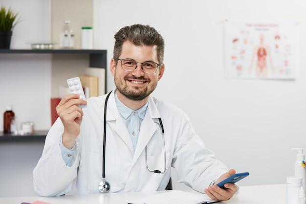 Médecin tenant des comprimés, beau médecin ayant des pilules dans ses bras assis dans une armoire médicale et souriant