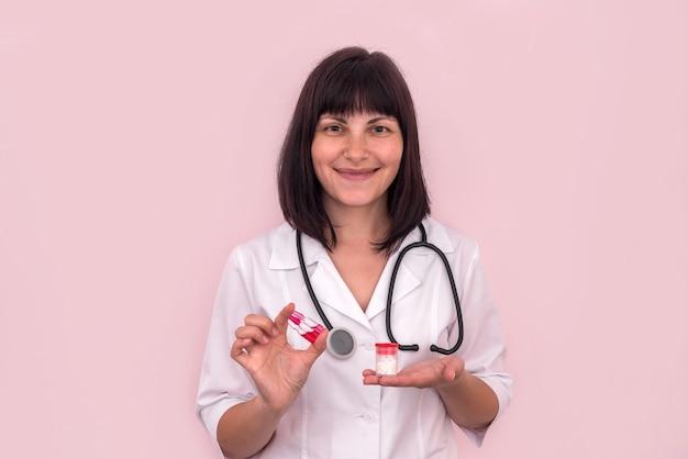 Médecin tenant des comprimés dans un récipient et des ampoules
